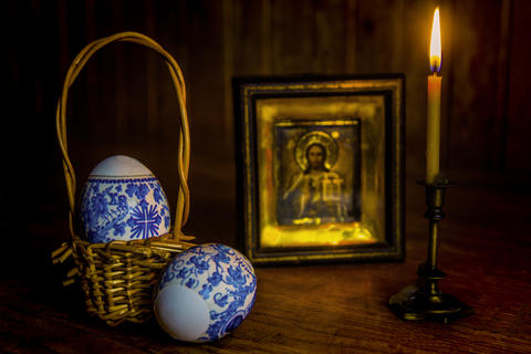 Easter eggs and a burning candle in a candlestick in front of an icon of Jesus Foto