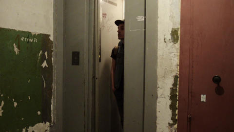 Man in cap with backpack walk out narrow elevator. Old house. Ragged walls Footage