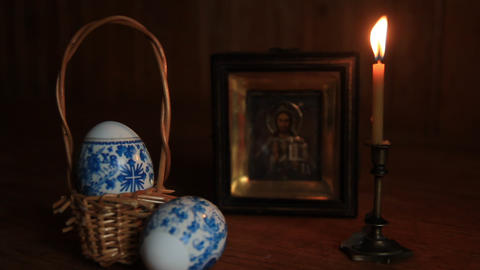 Easter eggs and a burning candle in a candlestick in front of an icon of Jesus 영상물