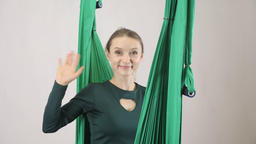 Young woman sits on a hammock smiling and waving her hand, a greeting gesture Footage