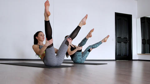 Two girls in the gym perform an exercise klubochalka. Pilate hassel. Lezhnaya on Footage