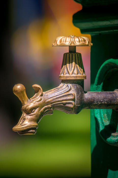 An antique water faucet in the city park フォト