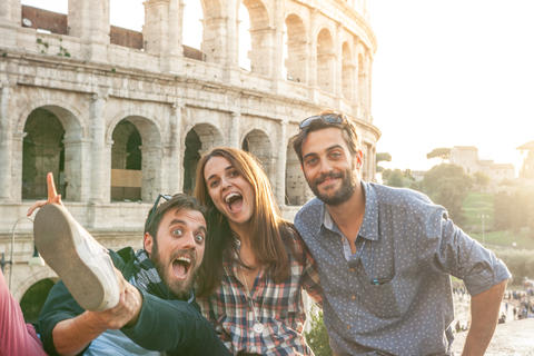 Three young friends tourists in front of colosseum in rome taking funny selfie フォト