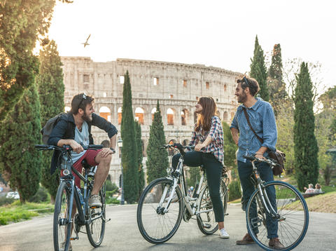 Three young friends tourists with bikes in colle oppio park in front of フォト