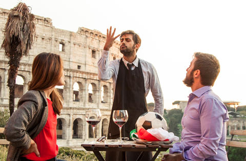 Elegant waiter serving football with italian flag to man of romantic young フォト