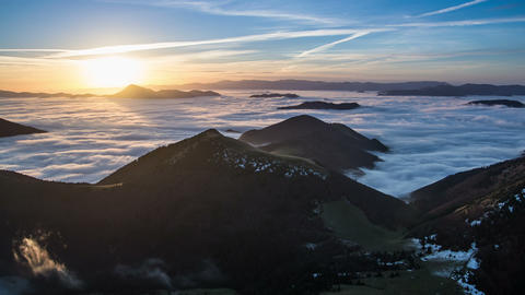 Colorful sunrise morning above mist clouds flows in mountain valley time lapse Footage