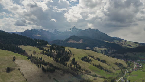 Aerial flight over spring landscape with clouds moving over mountains time lapse Footage