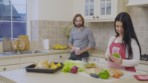 Handsome man kiss his wife while she's cooking salad Footage