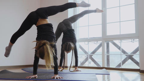Two girls stands on hands and makes an air split upside down Footage