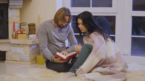 Married couple read the book near fireplace Footage