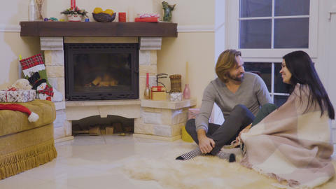 Happy married couple are talking near fireplace sitting on floor Footage