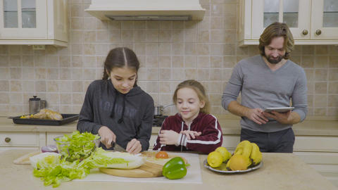 Two little girls learning to make a salad Footage