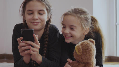 Cute little girls uses smartphones laying on floor Footage