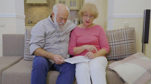 Old married couple discuss the rent bills sitting at sofa at home Footage