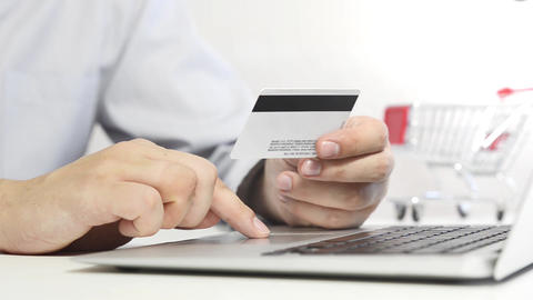 Man with laptop using credit card Footage