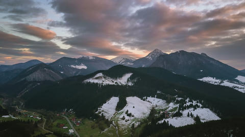 Evening colors over snowy mountains in early spring countryside landscape. Footage