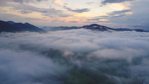 Aerial time lapse flight above mist clouds over beautiful evening nature colors Footage