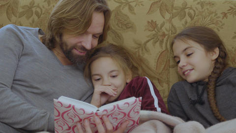 The father reads fairytale to daughters Footage