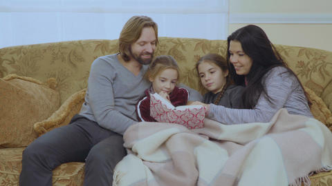 Happy family reads fairytale together on the sofa Footage