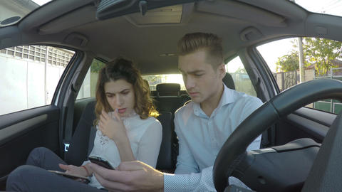 Young couple using smart phones in car and man shows phone to girlfriend and she Footage