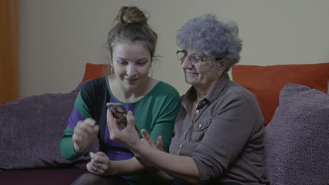 Granddaughter visiting and teaching her grandmother how to use her new Footage