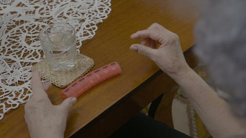 Elderly woman taking her medication from a daily pill planner with a glass of Footage