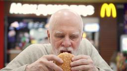 MOSCOW, RUSSIA- CIRCA JANUARY 2018: Hungry senior man eating hamburger at 영상물