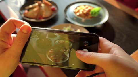 Girl makes a photo of meal on a smartphone in a cafe close up Footage