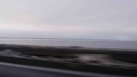 Driving automobile along vast sea on winter cloudy day Footage