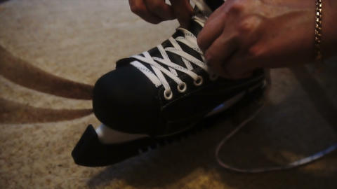 tying the white laces on skates,preparing to go on the ice Live Action