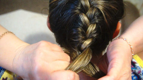 woman braids pigtails herself, slow motion ビデオ