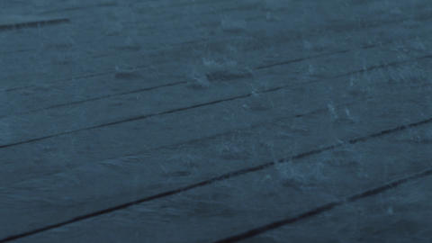 Harsh rain drops falling on wooden planks, dark evening outside Footage