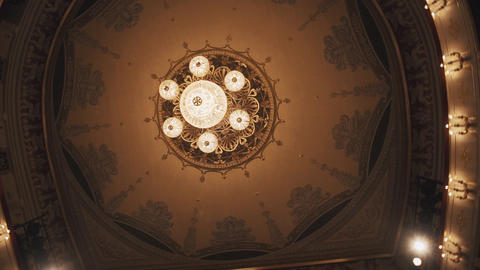 Luxurious golden chandelier on concert hall ceiling with murals Footage