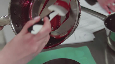 Confectioner puts simmered berries into backing dish using spatula at kitchen Footage
