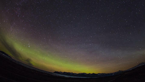 Time Lapse - Green and Pink Colored Northern Lights over the Mountains Footage