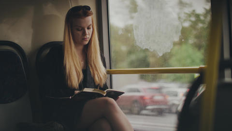 Young woman reading book and looking out window while driving in city bus Footage