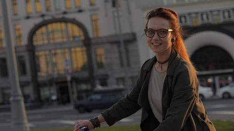 Portrait young woman riding a bicycle in evening city and looking into camera Footage