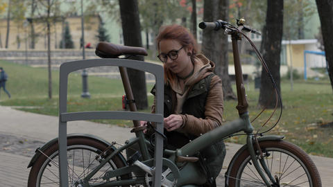Woman cyclist using key for closing lock on bicycle parking in city park Footage