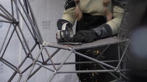 Woman in protective helmet using metall cutting machine in metalworking workshop Footage