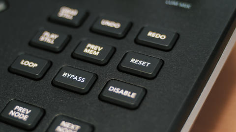 Male finger presses a RESET and BYPASS buttons on the keyboard Footage