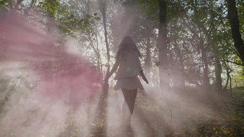Beautiful young model girl wearing a white dress spinning in a forest with smoke Footage