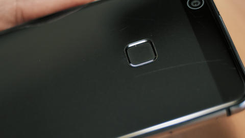 Man applies his finger to fingerprint scanner on the back of his mobile phone Footage