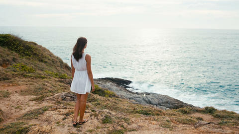 woman dreaming on the edge of the cliff at sunset on the background of the ocean Footage