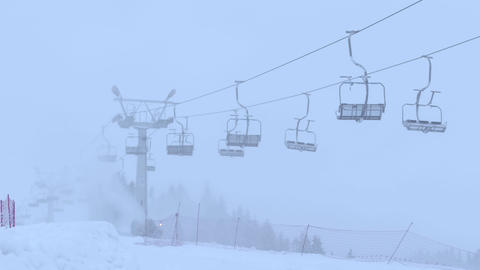Mountain ski slope and operating empty chairlift in the fog Footage