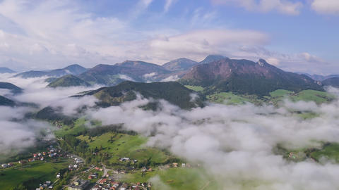 Morning flight above mist clouds in small village. Aerial slow motion time lapse Footage