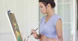 Attractive woman artist painting on her patio Footage