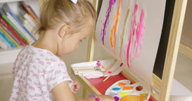 Cute little girl mixing paints for her painting Footage