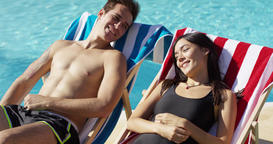 Young couple relaxing poolside in deck chairs Footage