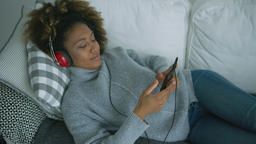 Young woman chilling on sofa with gadgets Footage
