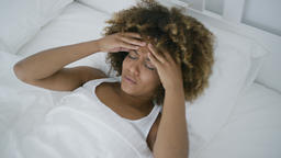 Young woman having headache lying in bed Footage